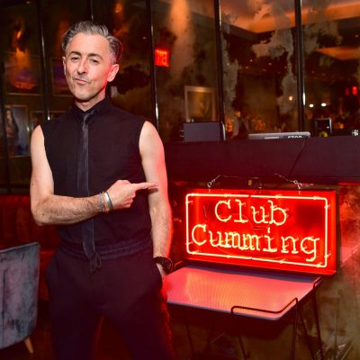 photo of Alan Cumming in front of the sign to his club