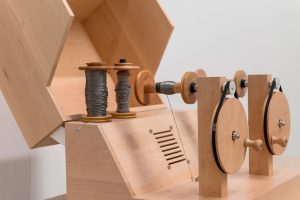 The Yarn Recorder can record and play sounds (Wooden device with two bobbins of yarn)