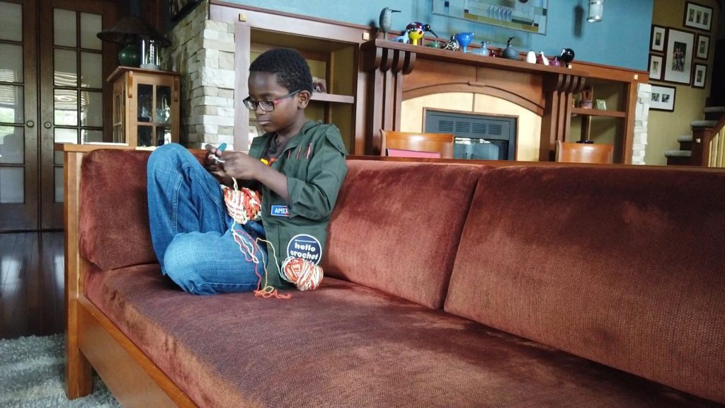Jonah Larson crocheting while sitting on a couch.