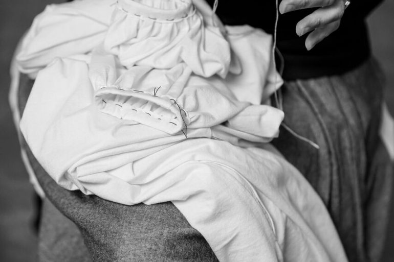 photo of fabric on lap with hands threading a sewing needle