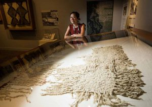 "Senior curator Tessa Campbell with a rare example of a blanket made from woolly dog hair and mountain goat hair at the Hibulb Cultural Center in Tulalip (Washington, USA). The blanket is part of the current exhibit ""Interwoven History, Coast Salish Wool."" (Andy Bronson / The Herald)"