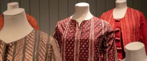 ditchling museum exhibit: women's work, shown are several garments from the exhibit on dress forms